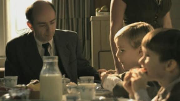Roland Freisler sitzt mit seinen Kindern am Frühstückstisch. (nachgestellte Szene)