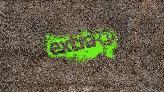 Eine Betonwand mit Extra3 Logo