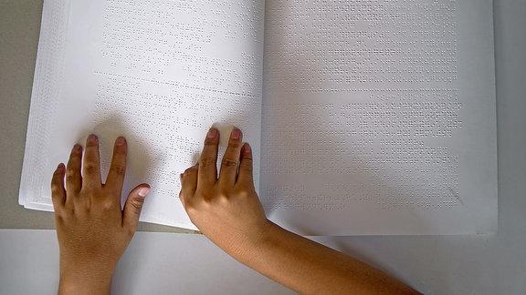 Hände ertasten die Blindenschrift in einem Buch