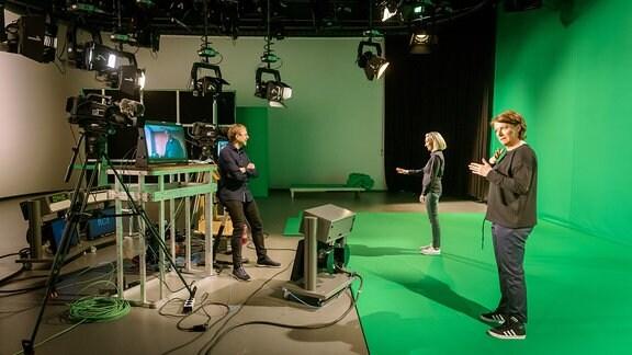 Katja Fischer (vorne im Bild) ist selbst gehörlos. Damit sie sich gut orientieren kann, ist ein hörender Gebärdensprachdolmetscher im Studio und gebärdet ihr wichtige Hinweise:  Peter Eichler steht zwischen den beiden Kameras auf Höhe der Monitore, die den Dolmetscherinnen den Jubiläums-Polizeiruf zeigen und von dem aus sie übersetzen.