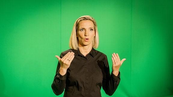 """Gebärdensprachdolmetscherin Antje Seifert hochkonzentriert bei der Arbeit. Sie steht vor """"Grün"""". In der Endfertigung einige Tage später wird der Film auf die grüne Fläche elektronisch projiziert."""