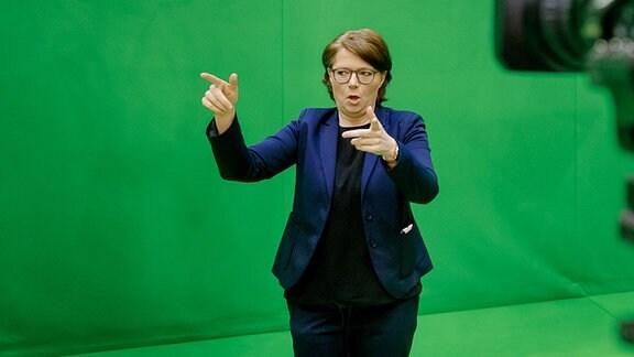 Die Gebärdensprachdolmetscherin Katja Fischer steht vor einer grünen Wand und gebärdet. Im Vordergrund rechts ist die Kamera zu sehen.