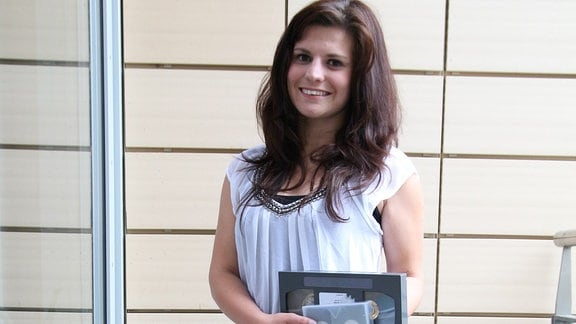 Junge Frau hält Videokassetten in der Hand