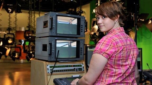 Junge Frau steht vor zwei kleinen Monitoren