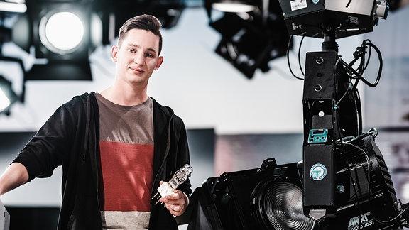Junger Mann steht in einem Fernsehstudio neben einer Kamera.