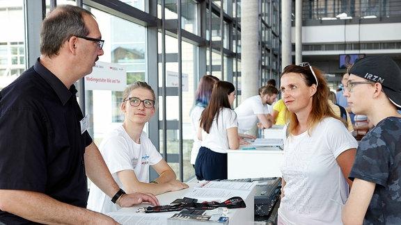 Eine Frau, zwei Jugendliche sprechen mit einem Mann an einem Informationsstand.