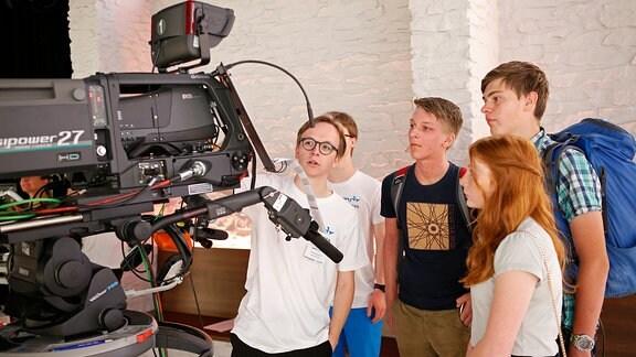 Ein Jugendlicher erklärt einer Gruppe Jugendlicher eine Fernsehkamera.