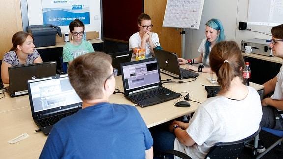 Mehrere Jugendliche sitzen an an einem Tisch vor Laptops.