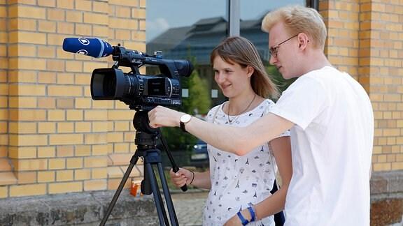 Ein junger Mann erklärt einer jungen Frau eine Video-Kamera.