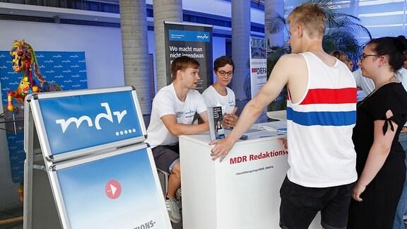 Ein junger Mann und eine junge Frau sprechen mit zwei Jugendlichen an einem Informationsstand.