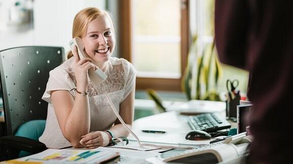 Junge Frau sitzt an einem Schreibtisch und telefoniert.