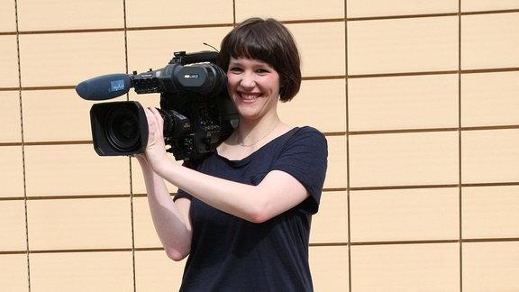 Junge Frau trägt eine Fernsehkamera auf der Schulter