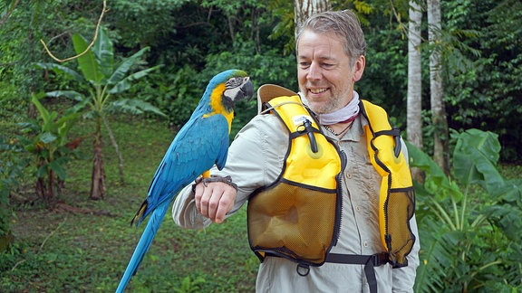 Ein Mann mit einem Papagei auf seinem rechtem Arm.