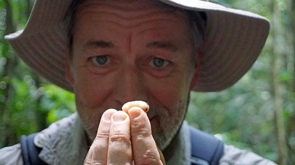 Ein Mann hält eine Larve aus der Motacú auf seinen Fingerspitzen in die Kamera.