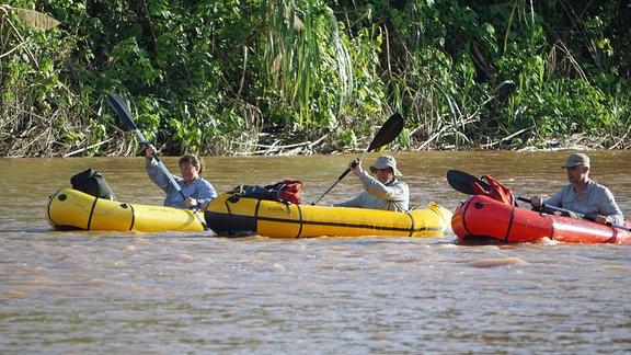 Personen in Schlauchbooten auf einem Fluss.