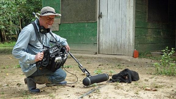 Ein Mann Ausrüstrung zuur Tonaufnahme hockt neben einem Klammeraffen