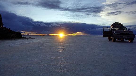 Sonnenaufgang Salzebene, ein Jeep mit offener Tür.