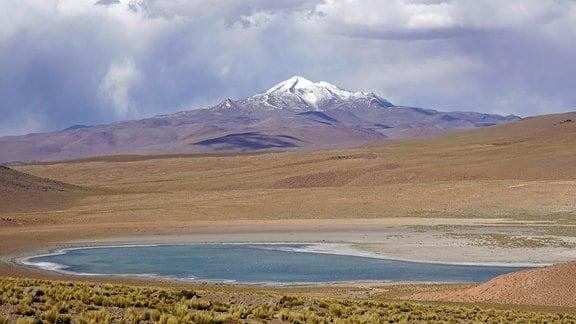 Schneebedeckter Berggipfel, davor flache Hochebene mit kleinem See