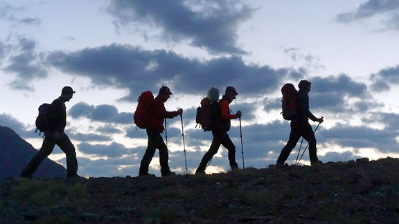 Das BIWAK-Team läuft hintereinander auf einem Bergkamm.