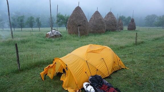 Ein Zelt steht neben einem Feld, Nebel verhüllt die fernere Landschaft.