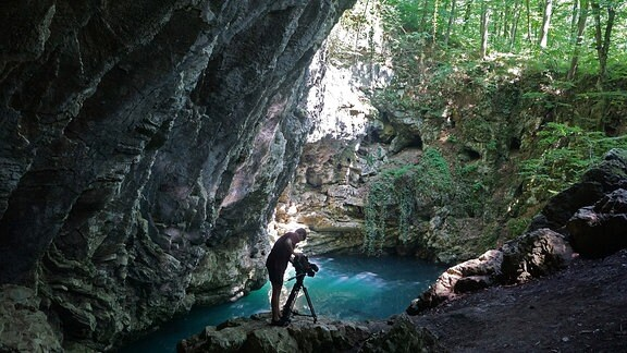 Ein Mann macht Filmaufnahmen eines kleinen See´s inmitten von Felsen.