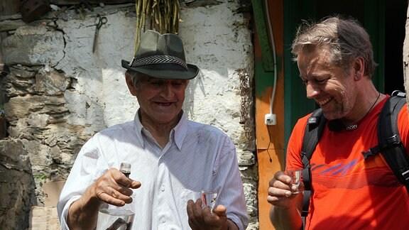Zwei Männer stoßen mit einem Glas Schnaps an.