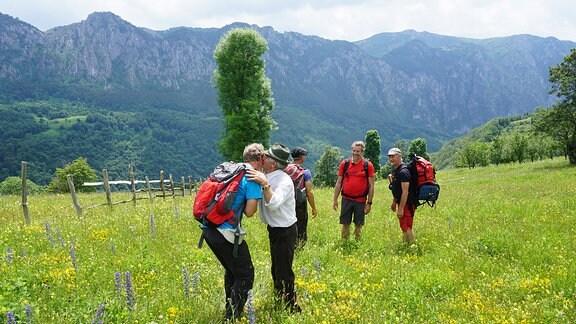 Menschen verabschieden sich herzlich, auf einer grünen Wiese stehend, im Hintergrund ein Bergmassiv.