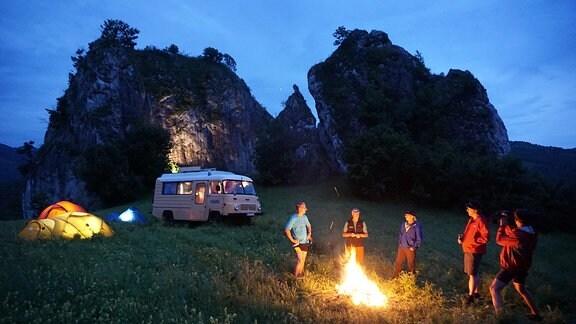 Menschen stehen um ein Lagerfeuer, im Hintergrund Zelte, ein Bus und schroffe Felsen.