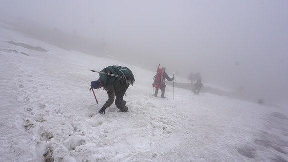 Wanderer klettern einen Schneebedeckten Hang hinab.