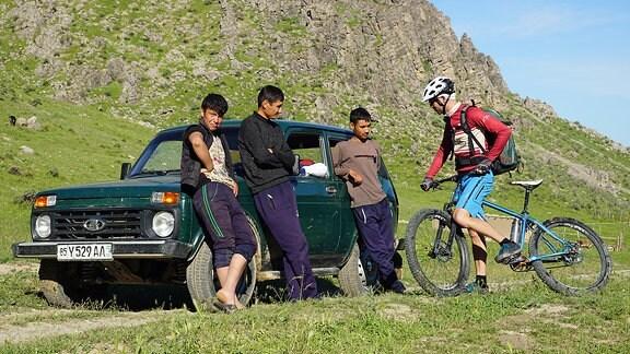 Drei Männer lehnen an einem Auto, daneben ein Mountainbiker
