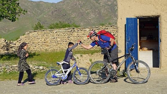 Ein Mountainbiker grüßt einen Jungen
