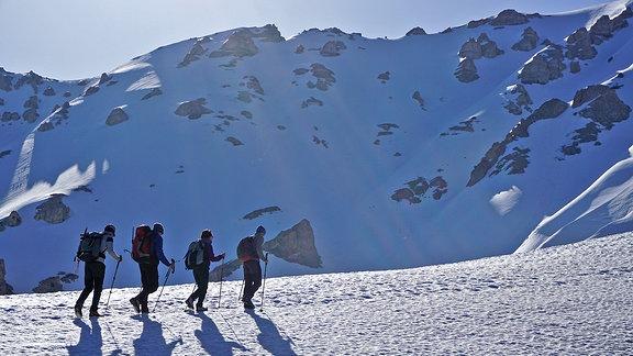 Vier Bergsteiger in einer Gebirgslandschaft