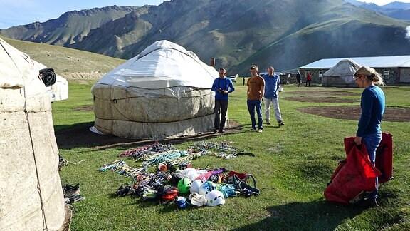 Bergsteiger neben Jurten sortieren ihre Ausrüstung in einer gebirgigen Steppenlandschaft