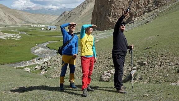 Zwei Männer und eine Frau sehen in einer Gebirgslandschaft nach oben