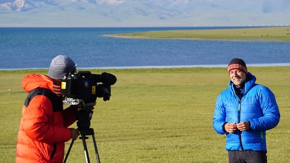 Ein Mann wird gefilmt, im Hintergrund ein See