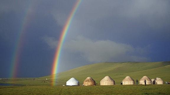 Ein Regenbogen über Jurten in einer Steppenlandschaft