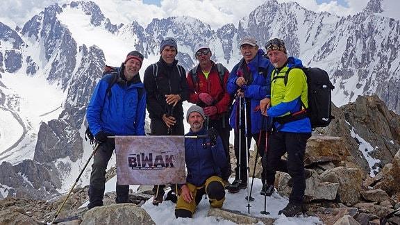 Bergsteiger auf einem Berggipfel mit dem Biwak-Logo