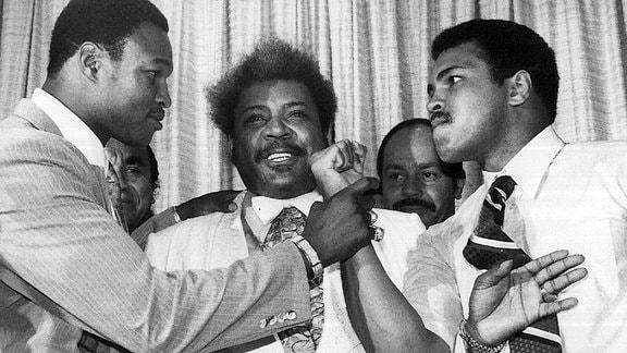 Muhammad Ali zielt mit seiner Faust auf Larry Holmes, dazwischen Don King.