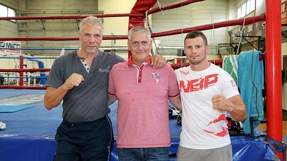 Drei Männer stehen mit vor einem Boxring und schauen lächelnd in die Kamera.