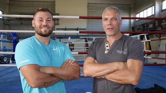 Zwei Männer stehen mit verschränkten Armen vor einem Boxring und schauen lächelnd in die Kamera.