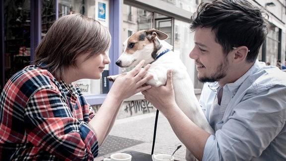 Ein Mann und eine Frau halten einen Hund in den Händen