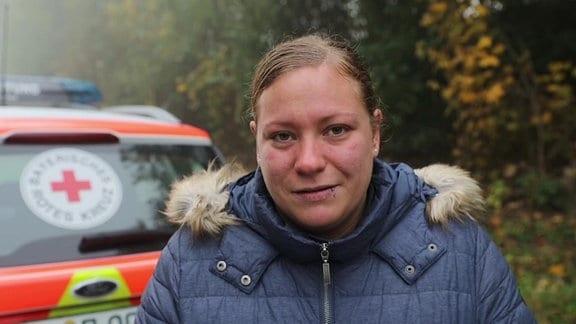 Ersthelferin Celine Hubersberger vor einem Rettungswagen - junge Frau mit blonden Haaren und blauer Jacke
