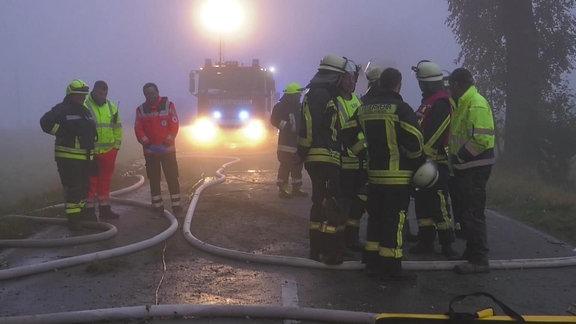 Feuerwehr-Rettungskräfte an einer Einsatzstelle - Schläuche auf der Straße