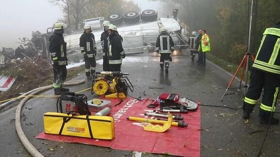 Umgekippter Milch-Laster mit Feuerwehrmännern samt Technik davor