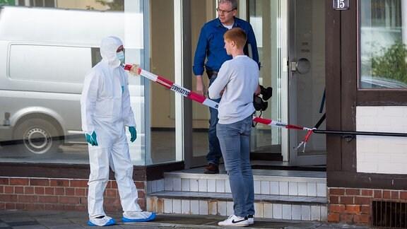 Zwei Mitarbeiter der Spurensicherung und ein Polizist stehen vor dem Eingang an einem Tatort.