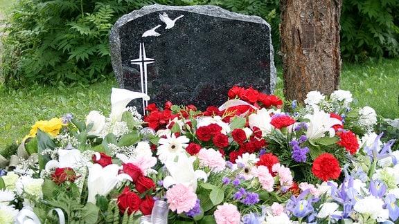 Blumen vor einem Grabstein.