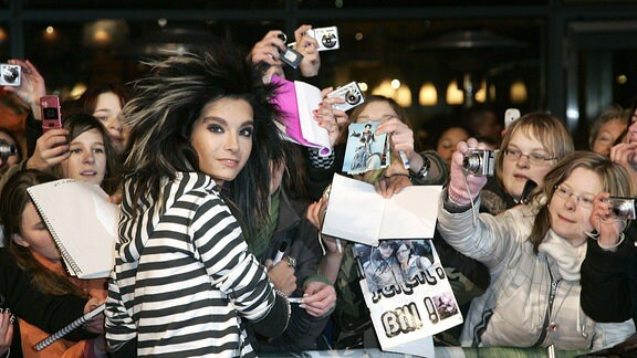 Bill Kaulitz gibt den Fans Autogramme und Blickt in die Kamera.