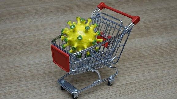 In einem Einkaufswagen befindet sich ein Coronamodell.