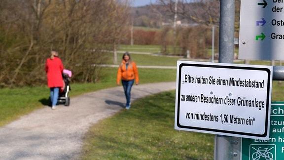 Schild mit Aufschrift 'Bitte halten Sie einen Mindestabstand zu anderen Besuchern dieser Grünanlage von mindestens 1,50 Metern ein'