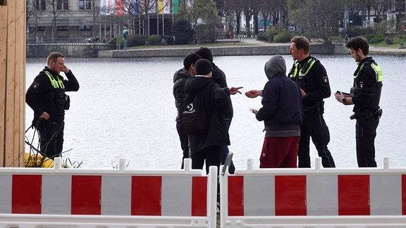 Vier Personen werden während des Kontaktverbots wegen der Coronakrise an der Alster kontrolliert.